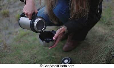 girls hands with thermos and cup hot tea - girl with thermos...