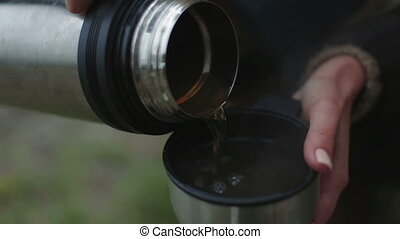pour tea from a thermos closeup - woman pours tea from a...