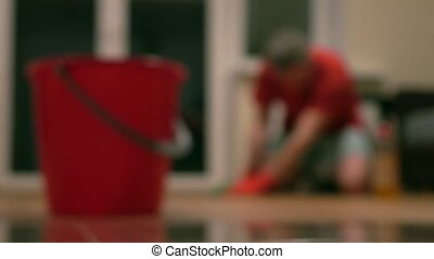 Blurred man in red tshirt cleaning up the room. 4K bokeh...
