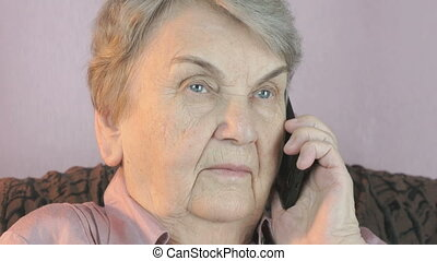 Elderly woman talks on smartphone with smile - Elderly woman...