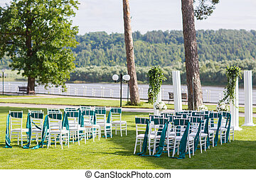 White wedding chairs with green and emerald ribbon outdoors