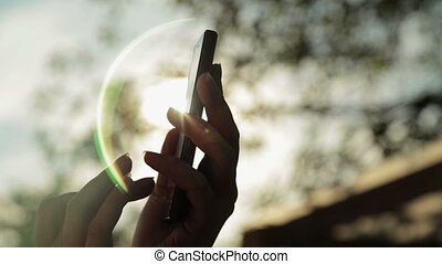 Silhouette of woman hands with smart phone at sunset