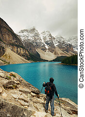 Moraine Lake - Hiker in Moraine Lake with snow capped...