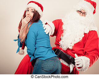 Santa Claus spanking woman with christmassy hat - Christmas...