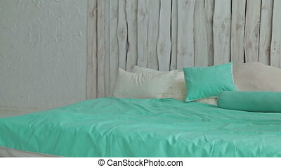 Cheerful curly woman falling on bed. Dolly shot - Cheerful...