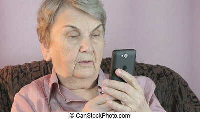 Old woman holding the cellphone indoors - An old woman...
