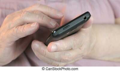 Close up of old wrinkled hands holding smartphone - Close up...