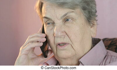 Old woman talking on mobile phone seriously indoors. Close...