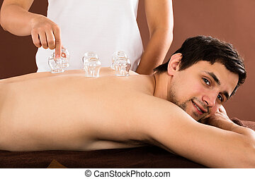 Man Receiving Cupping Treatment On Back - Relaxed Young Man...