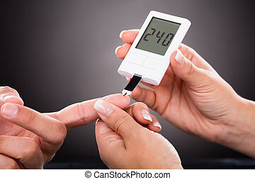 Doctor Checking Patient's Sugar Level With Glucometer -...