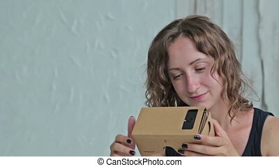 Young woman using Virtual Reality Glasses and sitting on the...