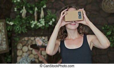 Young curly woman using Virtual Reality Glasses - Young...
