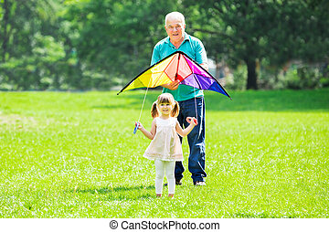 Granddaughter And Grandfather Flying Kite In Park - Happy...