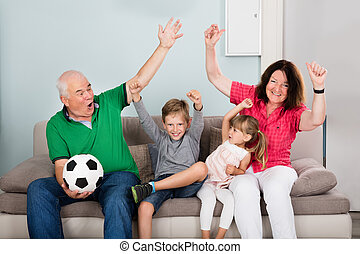 Family Watching Football Match On Television - Family Of...