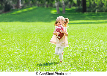 Little Girl Playing With Rugby Ball
