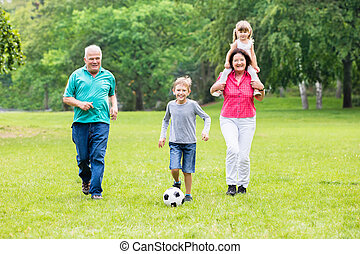 Grandparent And Grandchildren Playing Soccer Ball Together