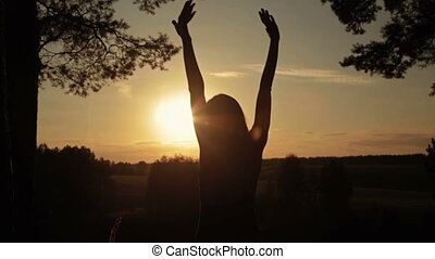Silhouette of woman in the forest on the sunset. Freedom concept.
