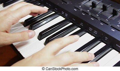 Woman playing a synthesizer - woman's hands playing on a...