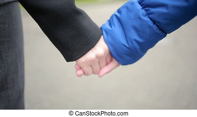 mother and daughter walking on the street. cold autumn. joined hands