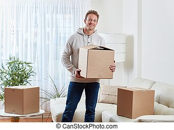 dwelling - Happy man with moving box at new cozy apartment