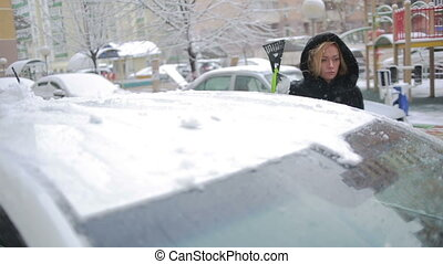 woman cleans snow from car