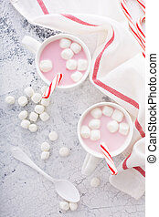 Peppermint hot chocolate with candy canes in a bright white...