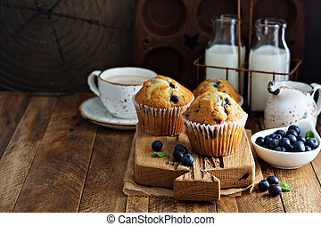 Freshly baked blueberry muffins in a rustic setting with...