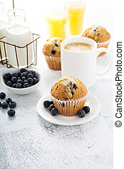 Bright and airy breakfast with blueberry muffin, big cup of...