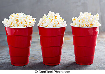 Popcorn in red cups - Tasty salted traditional popcorn in...