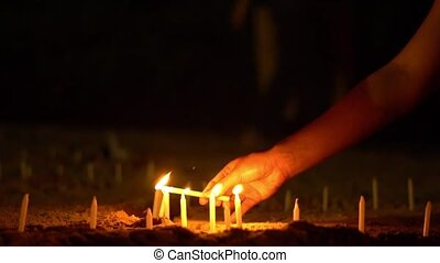 Asian candles on sand in religious ceremony , windy. People light candles. Slow motion