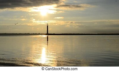 Sunrise over harbor with lighthouse. - Dramatic sunrise over...