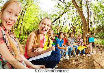 Laughing kids sitting on a log in the summer camp - Portrait...