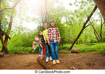 Cute kids standing on a log in the forest - Five cute boys...