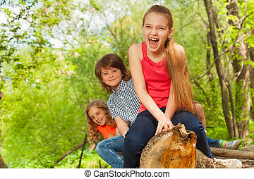 Smiling kids sitting on a log in the summer park - Portrait...