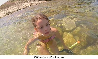 Girl in the sea dons fins. - A girl sits in the water of the...