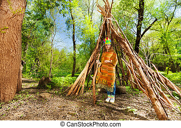 Cute girl in Indian costume standing at the tepee - Portrait...