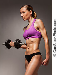 Young slim fit woman with dumbbell portrait