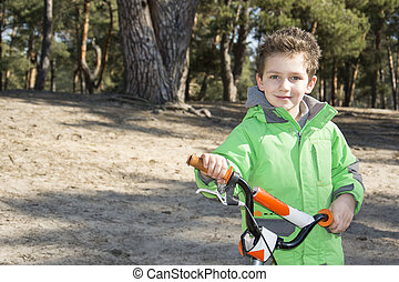 Happy baby funny little boy standing with his bicycle in a pine forest.