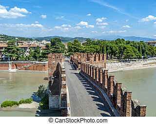 people at old bridge in Verona over Adige river -...