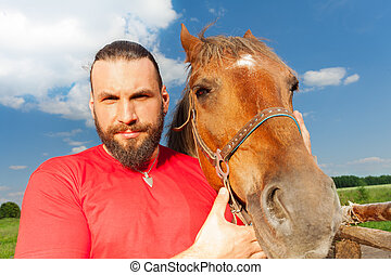 Close-up portrait of happy man with his bay horse
