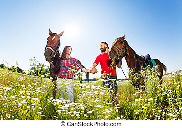 Loving couple walking with their purebred horses