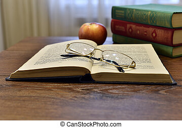Open book with glasses, apple and stack of books