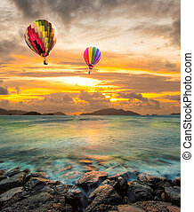 Hot air balloon over the sea at Sunset with dramatic sky background