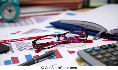 Glasses And Pen On Start Up Report - Office Desktop With Red...
