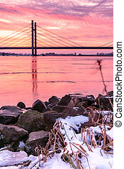Dutch suspension bridge over the river IJssel near the city of Kampen in the Netherlands. A very beautiful sunrise during winter