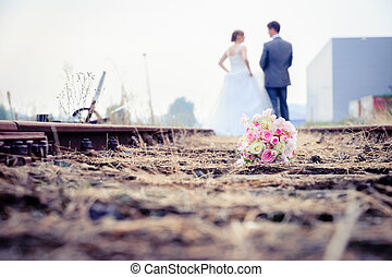 Newlywed couple walking on the rails of a pair of railroad...