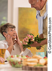 Bouquet of roses to surprised wife - Senior man giving a...