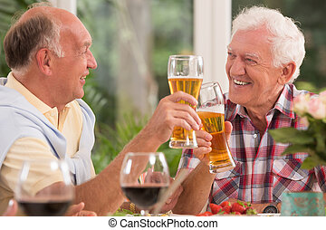 Senior friends drinking a beer