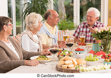 Group of happy seniors eating a dinner, drinking beer and...