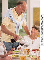 Senior man pouring glass of wine during evening meal with...